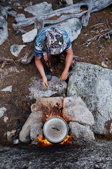 O homem construiu uma fogueira na floresta na natureza.