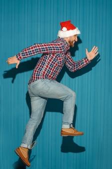 O homem correndo de natal usando um chapéu de papai noel