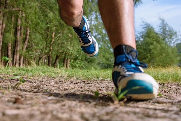 O homem correndo perto pernas e pés