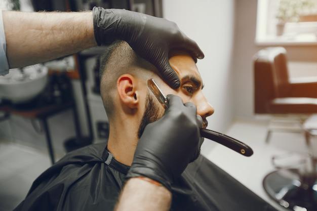 O homem corta a barba na barbearia.