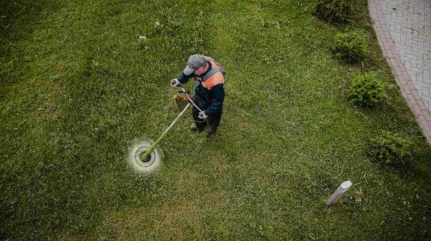 O homem cortador de grama corta a grama a vista de cima
