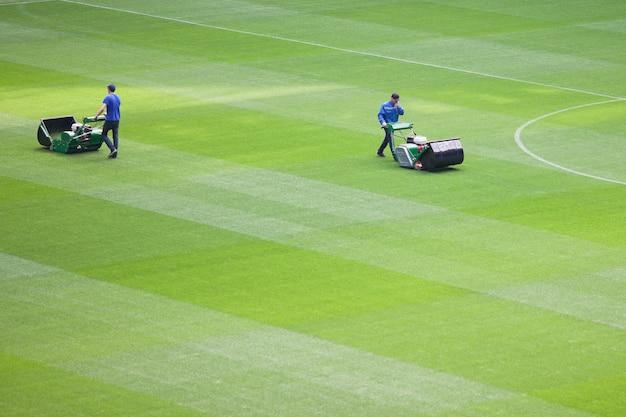 O homem cortador de grama corta a grama em um estádio de futebol.