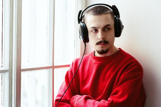 O homem cruza os braços enquanto ele escuta a música no peitorelado da janela