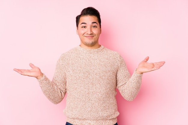 O homem curvilíneo novo que levanta em uma parede cor-de-rosa isolada faz a escala com braços, sente-se feliz e confiante.