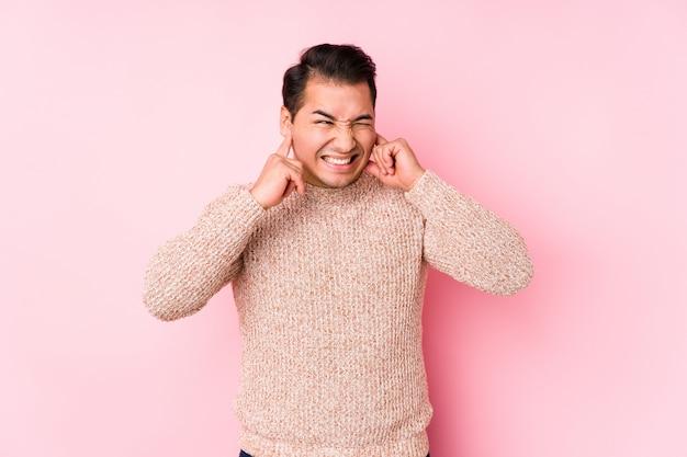 O homem curvilíneo novo que levanta em uma parede cor-de-rosa isolou as orelhas de coberta com as mãos.