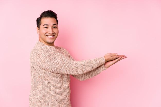 O homem curvilíneo novo que levanta em uma parede cor-de-rosa isolou guardar um espaço da cópia em uma palma.