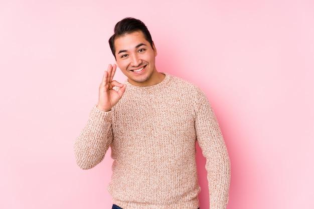 O homem curvilíneo novo que levanta em uma parede cor-de-rosa isolou mostrar alegre e seguro mostrando o gesto aprovado.