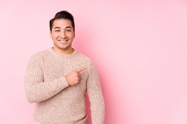 O homem curvilíneo novo que levanta em uma parede cor-de-rosa isolou o sorriso e apontar de lado, mostrando algo no espaço em branco.