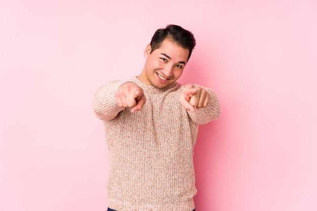O homem curvilíneo novo que levanta em uma parede cor-de-rosa isolou os sorrisos alegres que apontam para a parte dianteira.