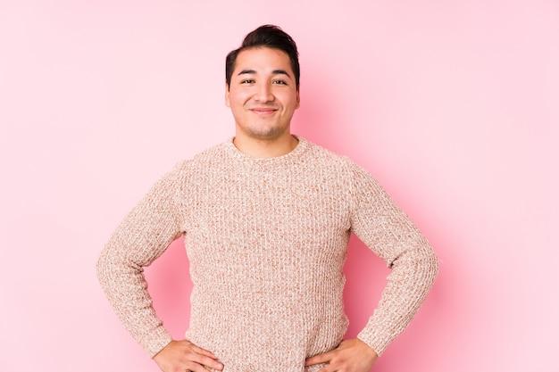 O homem curvilíneo novo que levanta em uma parede cor-de-rosa isolou seguro mantendo as mãos nos quadris.