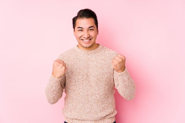 O homem curvilíneo novo que levanta em uma parede cor-de-rosa isolou torcendo despreocupado e entusiasmado. conceito de vitória