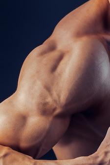 O homem da aptidão fundo ombro bíceps músculos peitorais tríceps fisiculturista em um fundo escuro demonstra a forma física para aulas no ginásio.