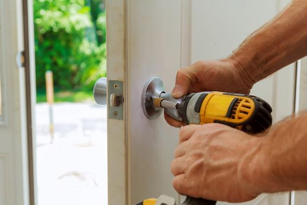 O homem da mão com chave de fenda instala a maçaneta da porta.
