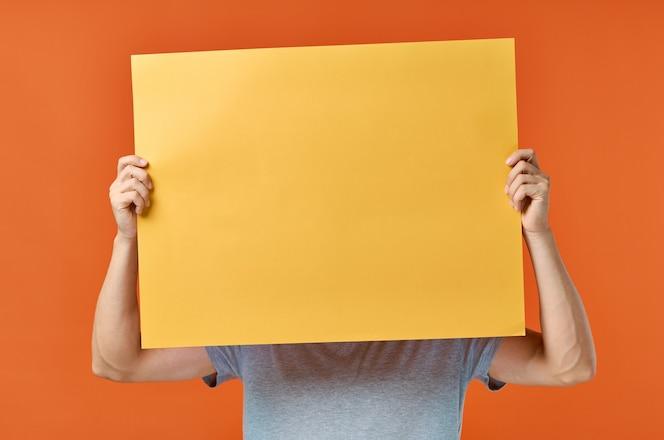 O homem da parede laranja do cartaz de marketing na vista cortada da parede.