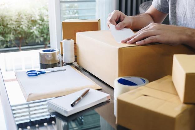 O homem da sme recebe o cliente do pedido e trabalha com o mercado em linha da entrega da caixa do tipo da embalagem no pedido de compra