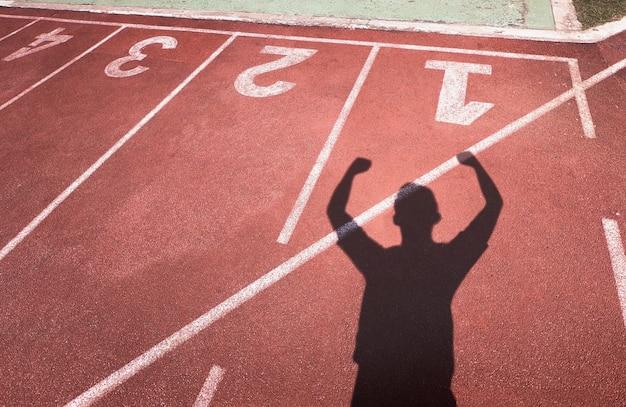 O homem da sombra está contente na vitória na trilha.
