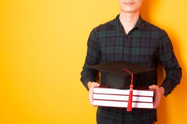 O homem da universidade está feliz com a graduação no fundo amarelo