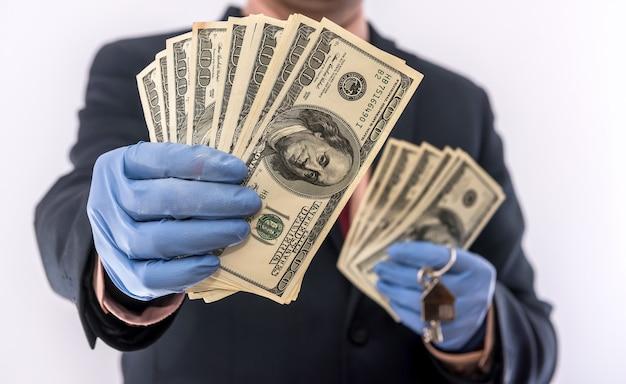 O homem da venda ou aluguel da casa com luvas médicas contém a chave da casa e o dólar ncov-2019