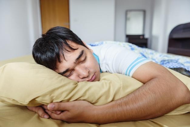 O homem de ásia dormindo na cama.