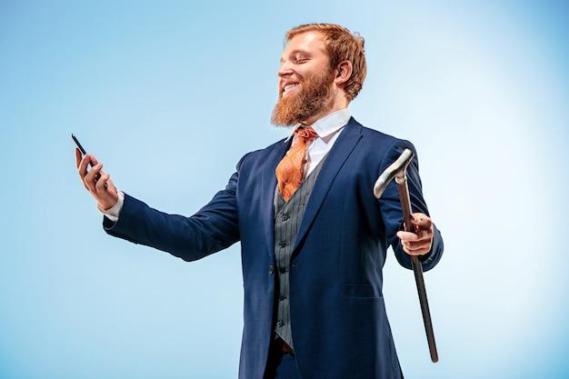O homem de bardo de terno segurando a bengala.