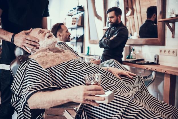 O homem de cabelo cinzento bebe o uísque na barbearia.