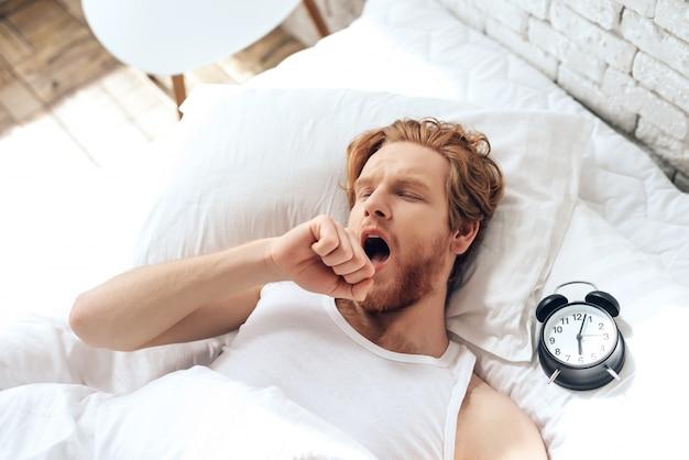 O homem de cabelo vermelho novo boceja encontrando-se na cama.