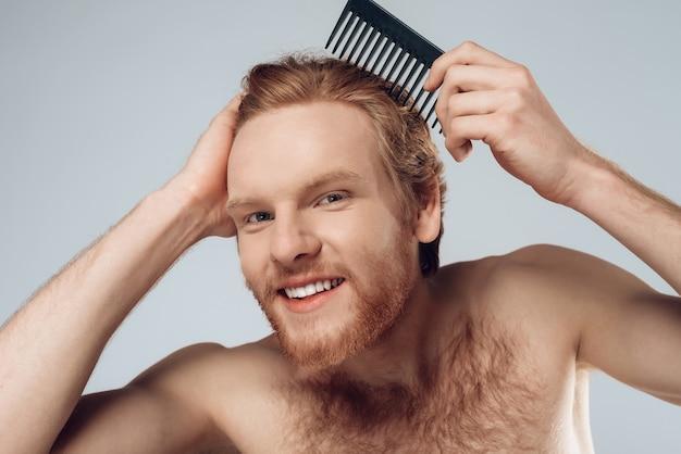 O homem de cabelo vermelho satisfeito penteia o cabelo com pente.