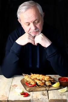 O homem de cabelos grisalhos ora antes de comer.