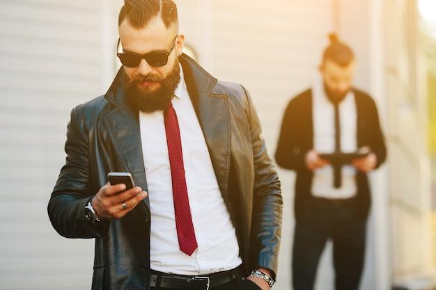 O homem de capa de couro verificando seu telemóvel