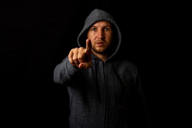 O homem de capuz toca o dedo em um fundo escuro.