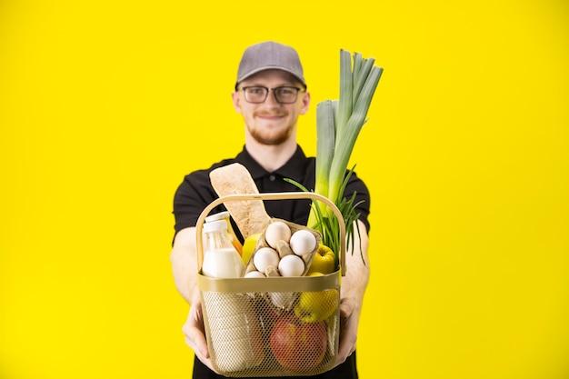 O homem de entrega de sorriso guarda a cesta com mantimentos, foco na cesta