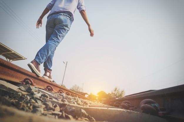 O homem de hipster anda nas faixas ferroviárias para encontrar o alvo da vida, efeito de tom vintage
