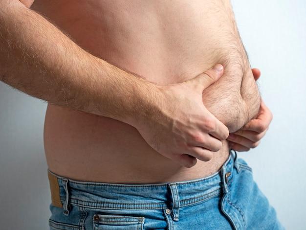 O homem de jeans aperta sua barriga peluda, flácida e gorda. t