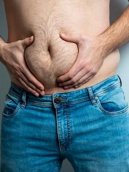 O homem de jeans aperta sua barriga peluda, flácida e gorda.