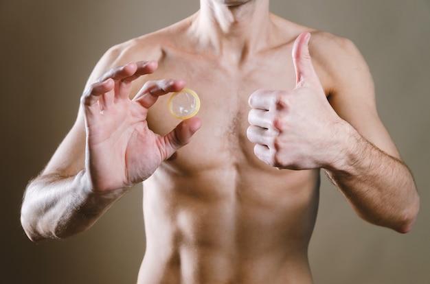 O homem de jeans preto tem um preservativo nas mãos e, com a outra mão, mostra o dedo para cima,
