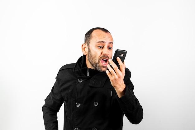O homem de meia idade com sobretudo grita irritadamente em seu telefone móvel, isolado no branco.