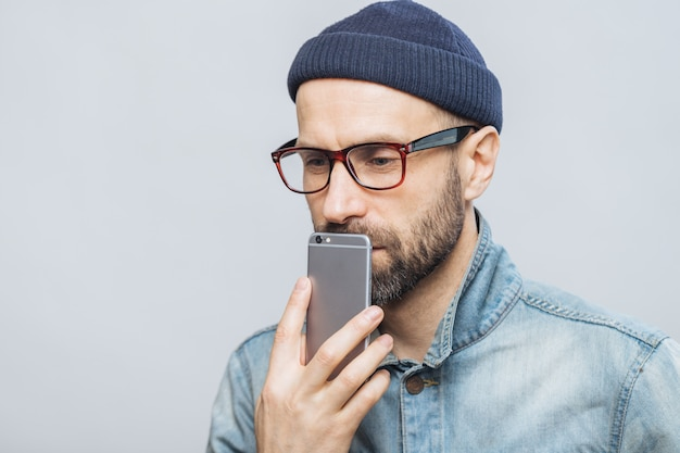 O homem de meia idade pensativo com restolho prende o telefone inteligente perto da boca, sendo profundo nos pensamentos