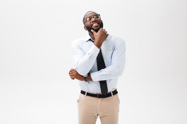 O homem de negócio afro-americano com vidros pensa no fundo branco isolado