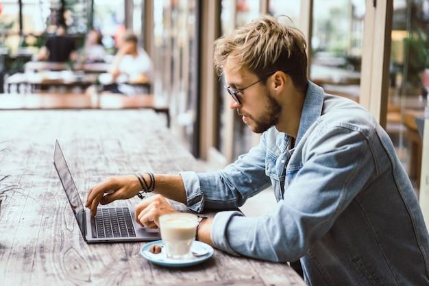 O homem de negócio atrativo novo em um café trabalha para um portátil, bebe o café.