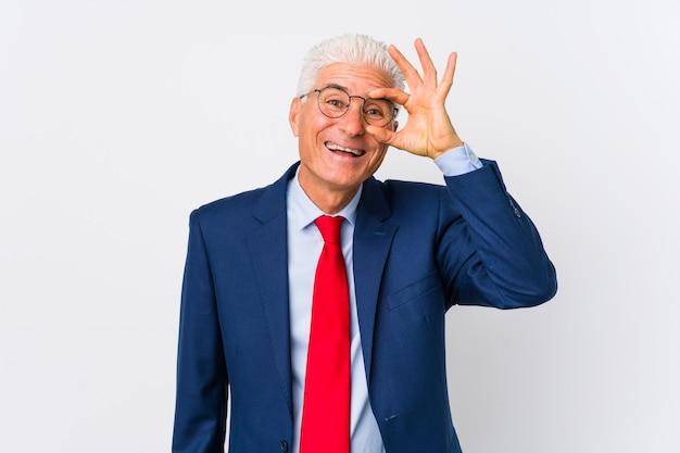 O homem de negócio caucasiano envelhecido médio isolou entusiasmado mantendo o gesto aprovado no olho.