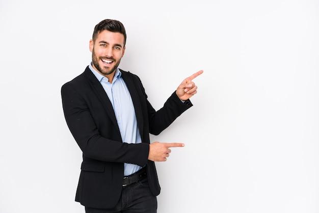 O homem de negócio caucasiano novo contra uma parede branca isolou apontar entusiasmado com os dedos indicadores ausentes.