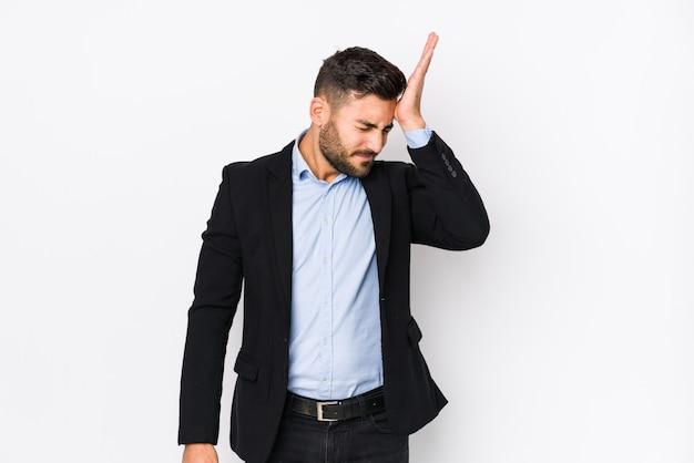 O homem de negócio caucasiano novo contra uma parede branca isolou o esquecimento de algo, batendo na testa com palma e fechando os olhos.