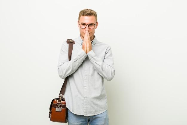 O homem de negócio caucasiano novo que guarda as mãos reza perto da boca, sente-se confiante.