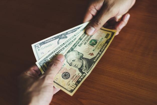 O homem de negócio dá o conceito do suborno do dinheiro - a pessoa entrega o homem que dá o dinheiro no fundo de madeira da tabela paga o dinheiro na entrega paga para receber o dinheiro