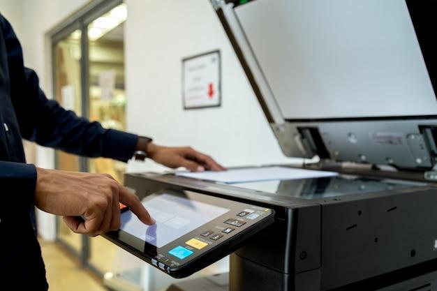 O homem de negócio entregue o botão da imprensa no painel da impressora, fontes da máquina da cópia do escritório do laser do varredor da impressora começam o conceito.