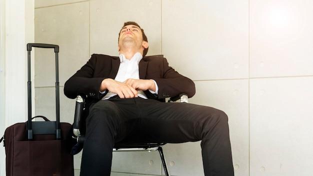 O homem de negócio está cansado e sente sonolento e senta-se na cadeira.