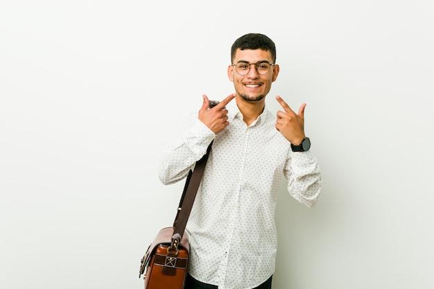 O homem de negócio ocasional latino-americano novo sorri, apontando os dedos na boca.