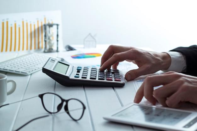 O homem de negócio prepara um relatório financeiro que trabalha com uma calculadora.