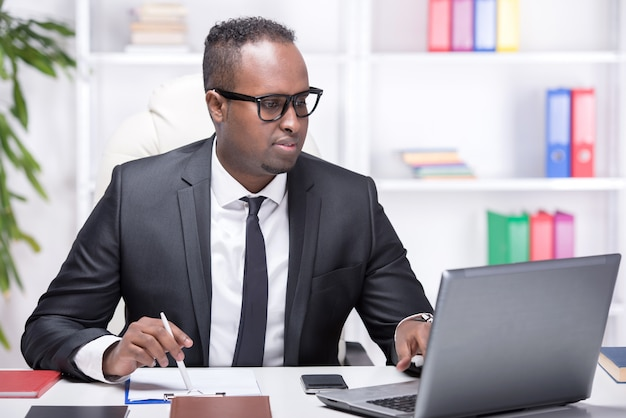 O homem de negócios africano novo está datilografando algo no portátil.