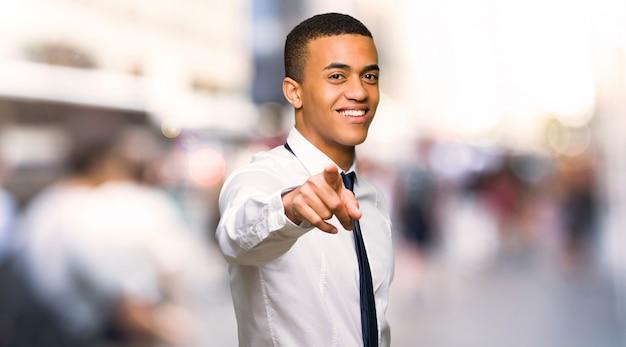 O homem de negócios afro americano novo aponta o dedo em você com uma expressão confiável na cidade